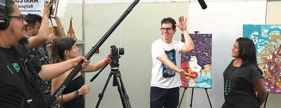 Ariana em ação com equipe de produção, filmando artista diante de seus quadros.